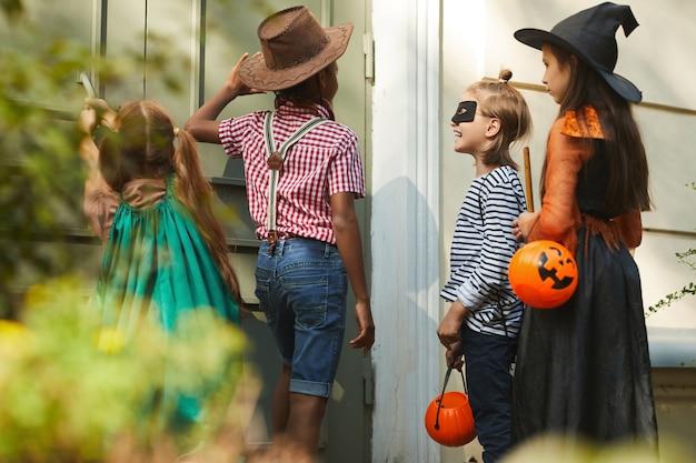 ハロウィーンの衣装を着た子供たちのグループがドアをノックしてトリックオアトリートを言う