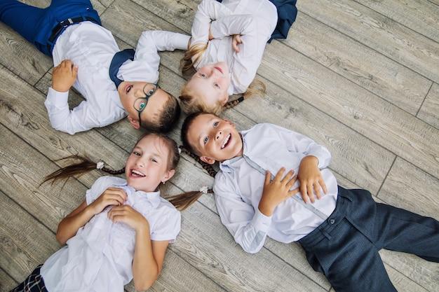 교복을 입은 아이들의 그룹은 바닥에 누워 밝고 아름다운 미소를 지었다