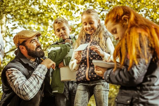 良い日に森で先生と一緒に学ぶ子供たちのグループ