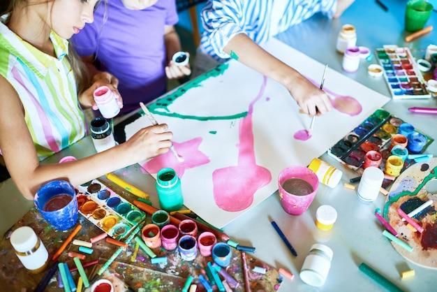 一緒に絵を描く子供たちのグループ