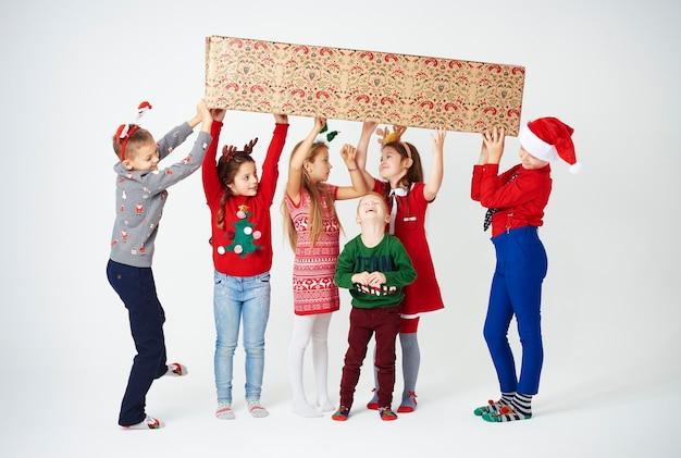 Группа детей готовится провести большую подарочную коробку