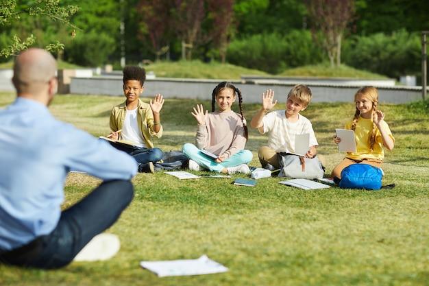 녹색 잔디에 행에 앉아 야외 수업에서 교사의 질문에 대답하는 동안 손을 올리는 어린이 그룹, 복사 공간