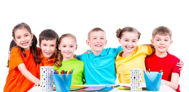 마커, 크레용 및 색종이가있는 테이블에 앉아있는 어린이 그룹