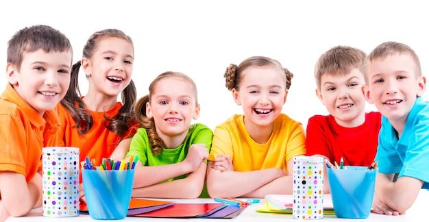 Группа детей, сидящих за столом с фломастерами, мелками и цветным картоном.