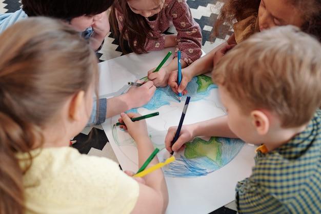 Группа детей, сидящих за столом и вместе рисующих картину цветными карандашами