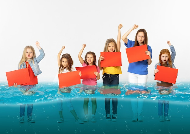 Группа детей с пустыми красными знаменами, стоящих в воде тающего ледника глобального потепления