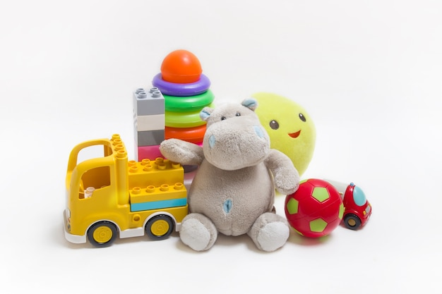 Группа детских игрушек на белом фоне. конструктор, пирамида, мяч и мягкие игрушки для развития детей