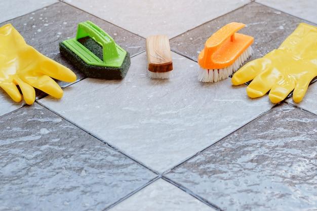 젖은 타일 바닥에 놓인 청소 장비 그룹.