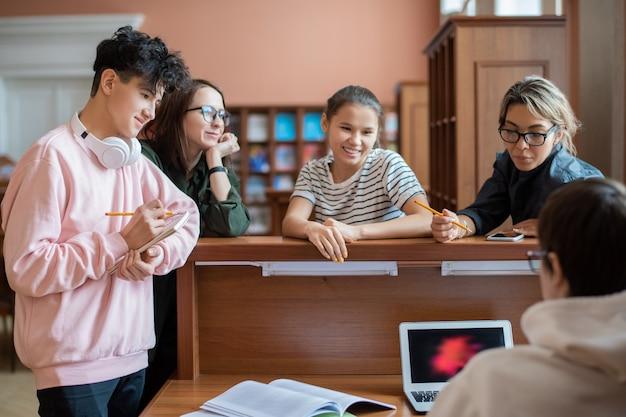 ノートパソコンの前でプログラマーのそばに立ってゼミの情報を見つけるのを手伝っている賢い大学生のグループ
