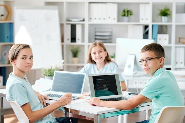 Группа умных учеников средней школы смотрит на вас в классе, сидя за столом перед ноутбуками