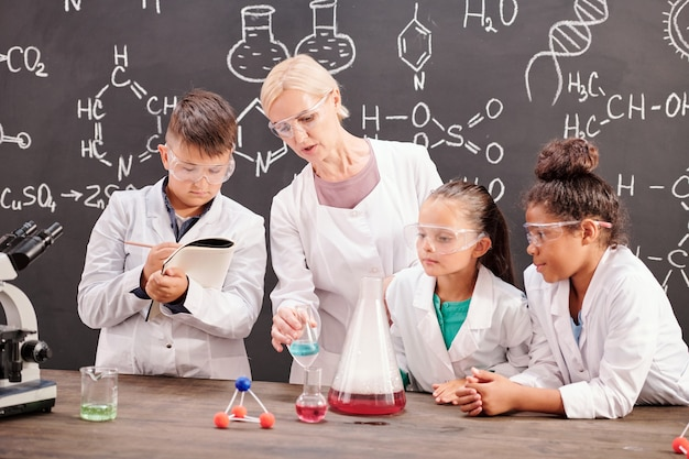 中学校の賢い生徒のグループがメモを取り、化学の授業で机のそばで化学実験を見せている先生を見ています