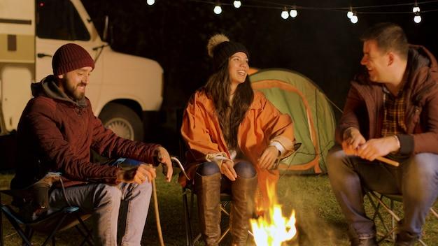 秋の寒い夜にキャンプファイヤーの周りで一緒にリラックスする親友のグループ。レトロなキャンピングカー。キャンプのテント。