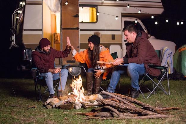 キャンプファイヤーの周りの親しい友人のグループは、バックグラウンドでレトロなキャンピングカーと笑っています。山でキャンプしている友達。