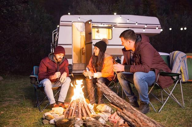 キャンプの火の周りでリラックスして山で一緒にキャンプする親しい友人のグループ。レトロなキャンピングカー。自然のきれいな空気。