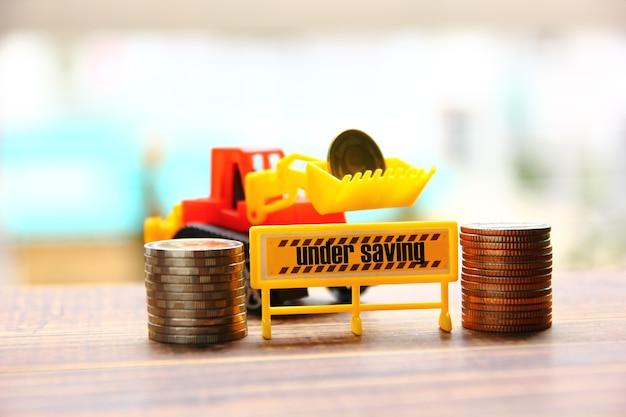 교통 표지, 돈 개념에 대한 절약 아래 건설 트랙터와 텍스트와 함께 나무 바닥에 쌓인 동전 그룹
