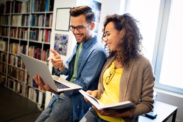 Группа студентов колледжа учится в школьной библиотеке. учеба, друзья, концепция образования.