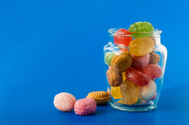 파란색 배경에 유리 항아리에 다채로운 사탕의 그룹입니다. 제과 및 과자 가게 개념입니다. 재고 사진.