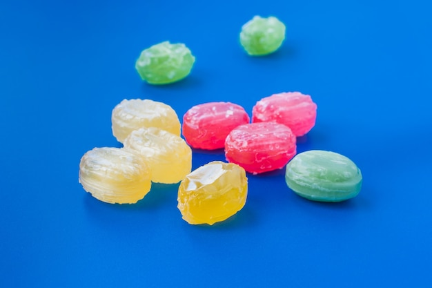 파란색 배경에 흩어져 있는 다채로운 사탕의 그룹입니다. 제과 및 과자 가게 개념입니다. 재고 사진.