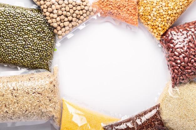 カラフルな様々な穀物やプラスチック製の豆類のグループは、copyspaceで白い壁にラップします。