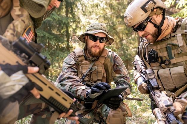 전투 계획을 분석하는 동안 원 안에 서서 지도를 사용하는 집중된 미국 군인 그룹