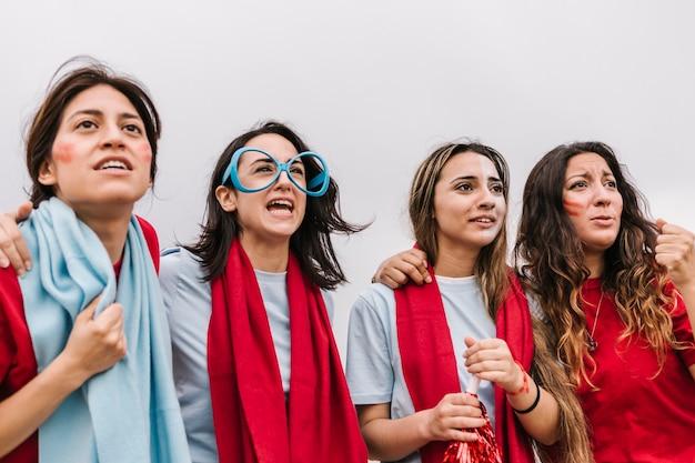 경기장에서 팀을 지원하는 집중된 여성 축구 팬 그룹