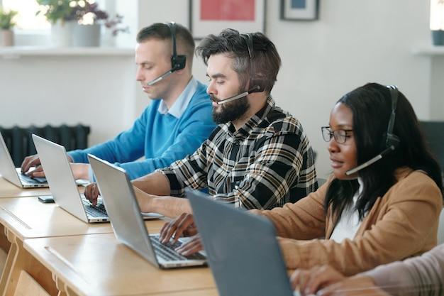 テーブルに座って、電話で製品を販売しながらラップトップを使用している集中した若い多民族のコールセンターエージェントのグループ
