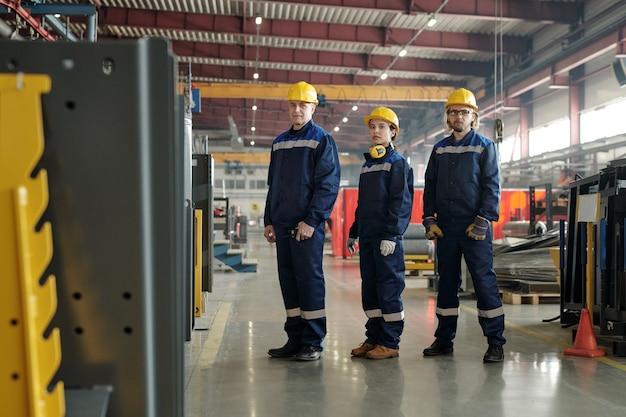 Группа уверенных в себе рабочих компрессорного завода в желтых касках и синей спецодежде, стоящих в ряду в заводской мастерской