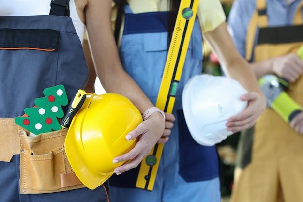 建設労働者のグループは、ツールとおもちゃのクリスマスツリーのクローズアップで保護ヘルメットを保持しています