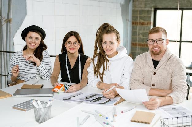 Группа современных креативных модельеров сидит за столом, работая над новой коллекцией на встрече