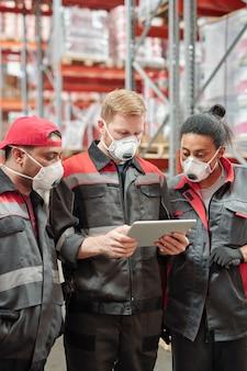 인공 호흡기와 작업복을 입은 현대의 다문화 창고 작업자 그룹이 태블릿에서 다양한 상품을 스크롤합니다.