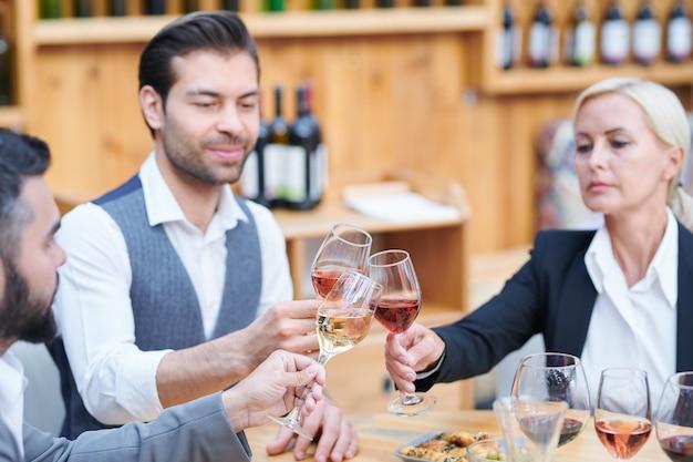 Группа современных виноделов, чокающихся за столом бокалами с различными сортами вина, работая в погребе