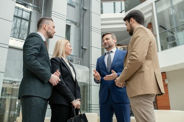 Группа контент-юристов разного возраста стоит в кругу и обсуждает новое дело в холле