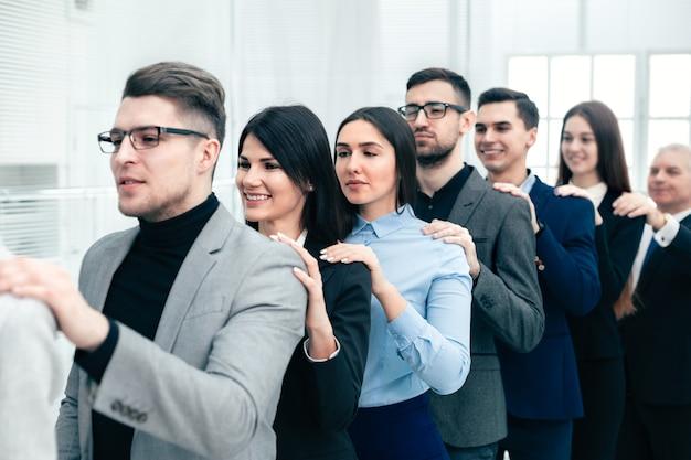 서로 뒤에 서있는 회사 직원의 그룹입니다. 팀워크의 개념