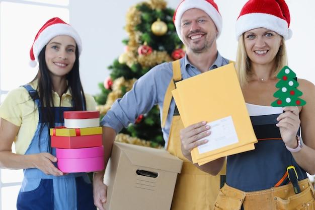 クリスマスツリーの近くに立って、たくさんのギフトボックスを持っているサンタクロースの帽子をかぶった宅配便のグループ。新年の贈り物の概念の速い配達
