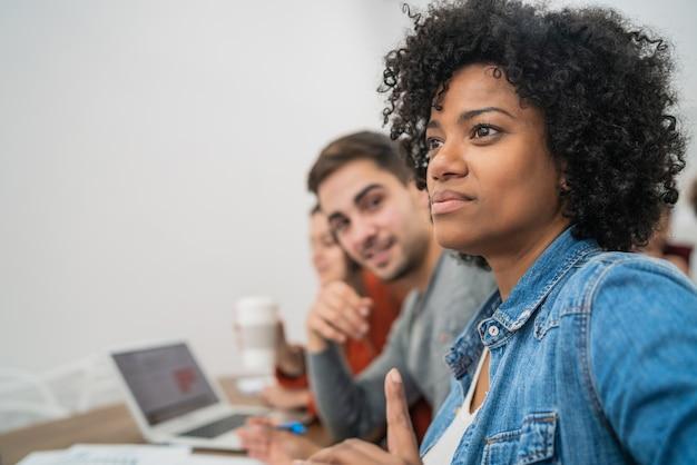 オフィスミーティングで演説する同僚の話を聞いている創造的なビジネスマンのグループ。ビジネスとブレーンストーミングの概念。