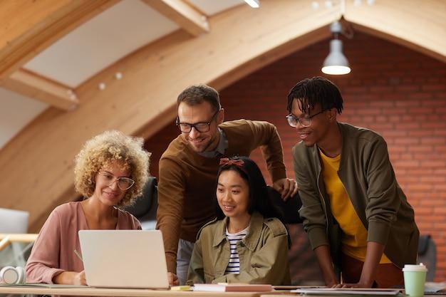 オフィスで一緒にラップトップでビジネスプレゼンテーションをオンラインで見ている創造的なビジネスの人々のグループ