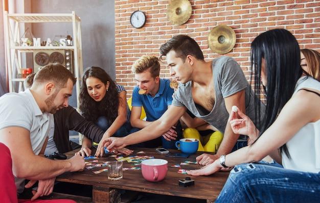 Группа творческих друзей, сидя на деревянный стол. люди веселятся во время игры в настольную игру