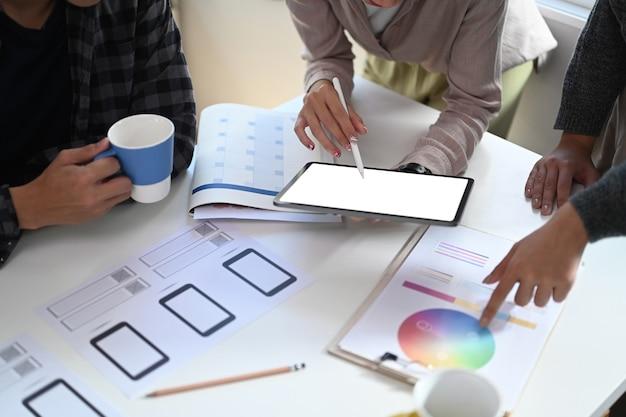 カラーパレットで色を選択し、会議室でデジタルタブレットを操作するクリエイティブなグラフィックデザイナーのグループ。