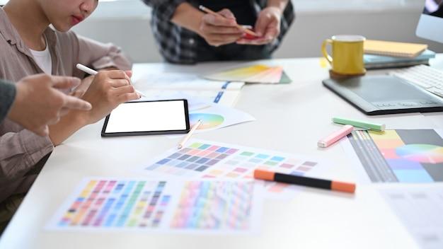 顧客プロジェクトのカラーパレットで色を選択し、会議室でデジタルタブレットを操作するクリエイティブなグラフィックデザイナーのグループ。