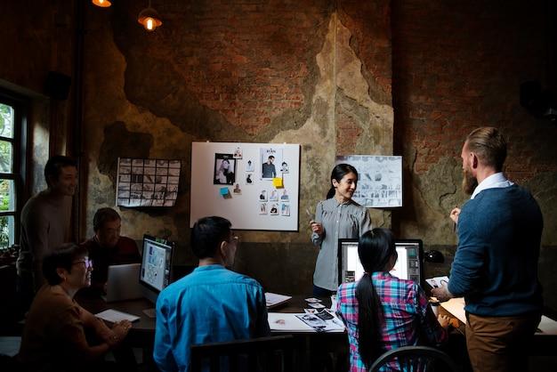 一緒に働いてブレインストーミングする創造的な人々のグループ
