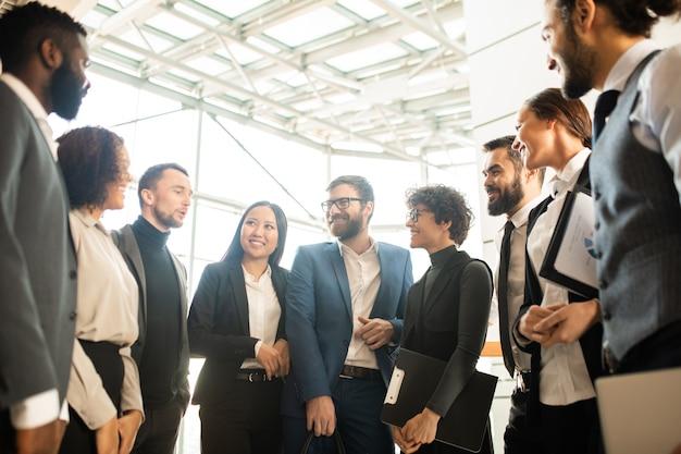 輪になって新しいキャンペーンについてブレインストーミングしている創造的な若い多民族のビジネス同僚のグループ