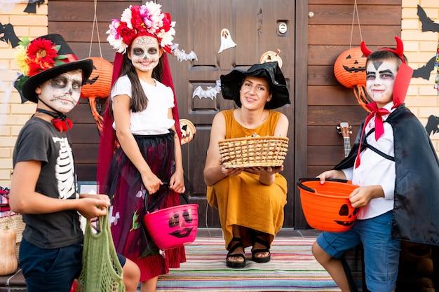 Группа милых детей в костюмах на хэллоуин, окружающих молодую улыбающуюся женщину с корзиной угощений, сидящих на корточках у двери