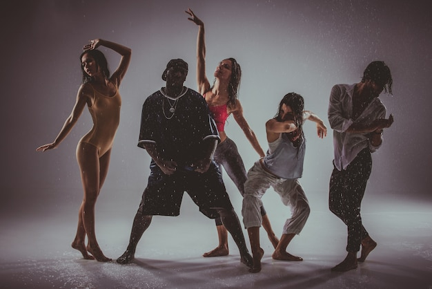 Группа танцоров, танцующих на сцене с эффектом дождя