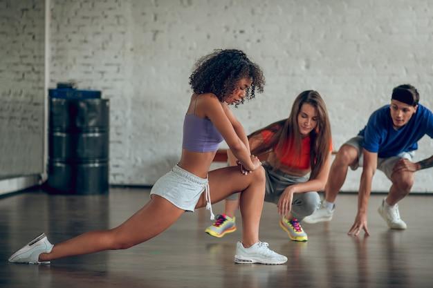 Группа танцоров, улучшающих гибкость перед репетицией
