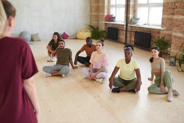 床に座ってヘルスクラブでのトレーニング中にインストラクターの話を聞いているダンサーのグループ