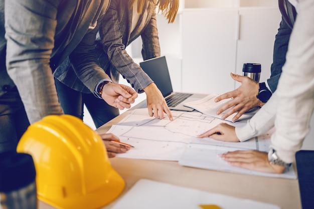 Группа преданных трудолюбий очень мотивирует архитекторов, которые смотрят и указывают на чертежи на столе внутри здания, которое они хотят обновить.