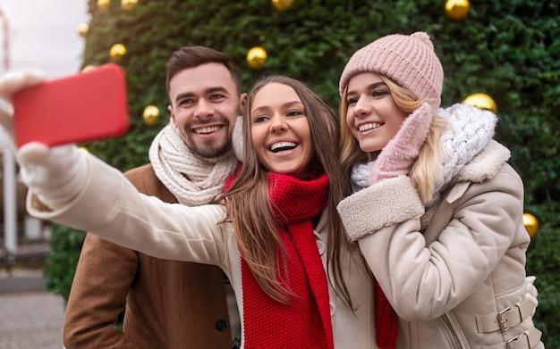 Группа счастливых молодых друзей в теплой одежде, стоящих на фоне зеленой елки и делающих селфи на смартфоне, проводя отпуск вместе в городе