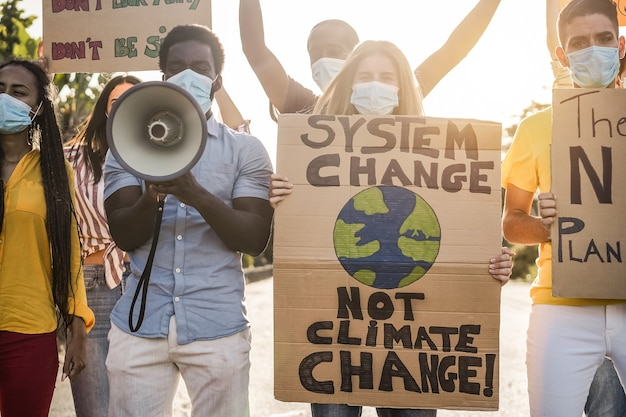 코로나바이러스 발생 중 기후 변화에 대한 다른 문화 및 인종 항의에서 길을 가는 시위대 - 배너에 초점