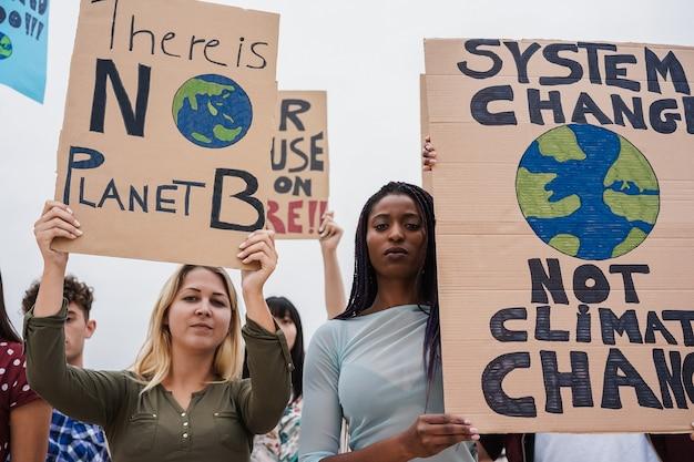 道路上のデモ隊のグループ、異なる文化と人種の若者が気候変動のために戦う-アフリカの女の子の顔に焦点を当てる