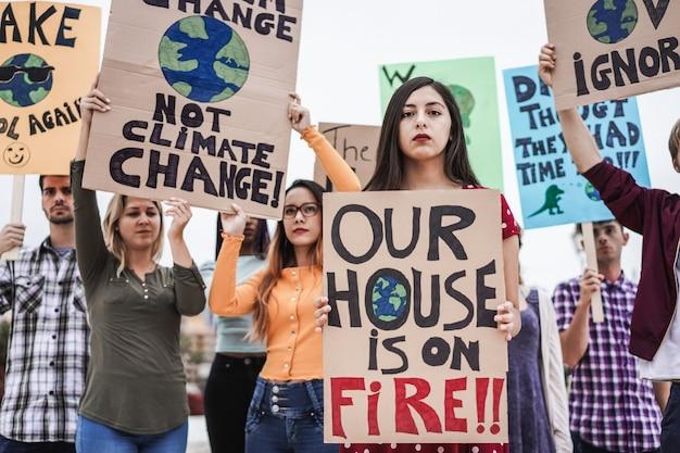 도로의 시위대 그룹, 다른 문화 및 인종의 젊은 사람들이 기후 변화를 위해 싸 웁니다-중심 소녀 얼굴에 초점